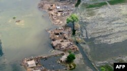 Pakistani villagers seek refuge on a dry patch in the flood-hit Jacobabad district of Sindh province, September 17, 2012.