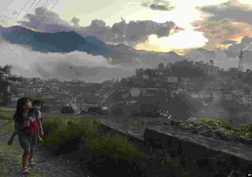 인도 동부 나갈랜드주도 코히마에서 동생을 안은 소녀가 언덕을 오르며 석양을 감상하고 있다.