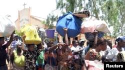 Des Togolaises avec des bagages sur la tête attendent de se faire enregistrer comme réfugiées au village voisin de Hilacondji, Bénin, 2 mai 2005.