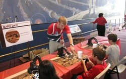 Dan Grunberg helps a young robot operator