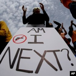 High school sophomore Dakotah Brown, 16, holds a sign at a rally for tighter gun laws, April 20, 2018 in Kansas City, Mo.