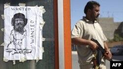 Pripadnik pobunjeničkih snaga pored crteža Moamera Gadafija na kontrolnom punktu u Tripoliju, 30. avgust 2011.
