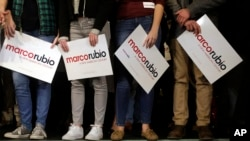 Supporters of Republican presidential candidate Senator Marco Rubio stand on a stage, holding placards before a campaign event in Exeter, New Hampshire, Feb. 2, 2016.