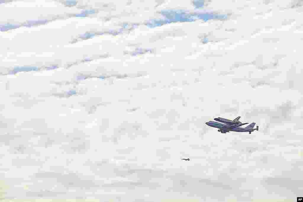 Phi thuyền con thoi Discovery được một máy bay phản lực 747 cõng trên lưng bay ngang qua Quảng trường Quốc gia ở thủ đô Washington ngày 17 tháng Tư năm 2012 (Hinh: A.Klein - VOA)