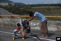Un migrante empuja un carro de bebé por una carretera mientras una caravana de miles de migrantes centroamericanos sigue su lento avance hacia la frontera con Estados Unidos, entre Niltepec y Juchitan, en el estado de Oaxaca, México, el 30 de octubre de 2018.