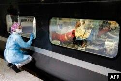 Seorang petugas medis mengawasi pasien Covid-19 di stasiun Gare d'Austerlitz saat mereka dievakuasi dari Paris ke daerah lain karena penuhnya rumah sakit di Paris.