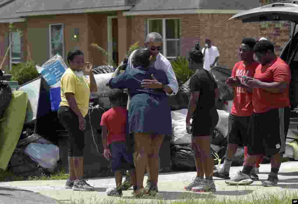 President Barack Obama greets residents as he tours Castle Place, a flood-damaged area of Baton Rouge, La., Aug. 23, 2016.