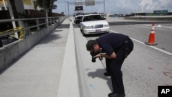 Un investigador fotografía una tarjeta de crédito del caníbal de Miami, Rudy Eugene, encontrada en la escena del crimen, en Miami.