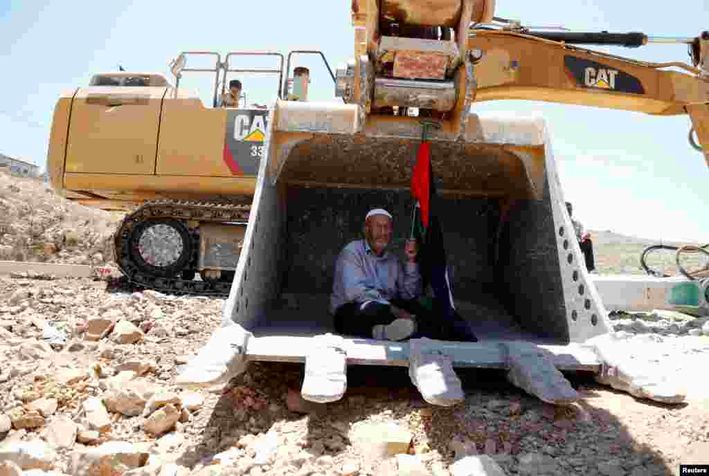 A man holding a Palestinian flag protests as he sits in the scoop of an Israeli excavator to prevent it from clearing his land near the village of Deir Qaddis near the West Bank city of Ramallah.