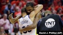Košarkaši Golden Stejta Kevin Durent i Stef Kari grle se posle pobede nad Hjustonom u sedmoj utakmici finala Zapadne konferencije NBA plej-ofa, 28. maja 2018. (Foto: AP/David J. Phillip))