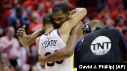 Kevin Durant des Golden State Warriors et son coéquipier Stephen Curry, après leur victoire sur les Houston Rockets, Houston, Texas, le 28 mai 2018.
