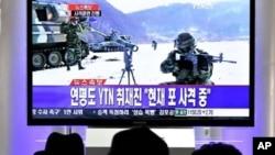 韩国人在观看电视实况转播的韩国军队实弹炮击演习
