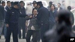 中國警員經常拘押上訪人士﹐圖為支持權利活動人士王荔蕻的支持者在北京法院門前遭警員拘趕。(資料圖片)