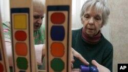 Nhân viên trong khu nhà của người cao tuổi chăm sóc cho một bệnh nhân bị suy giảm trí nhớ (phải)