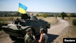 Ukrainian servicemen speak near an armored vehicle in their camp near Donetsk Sept. 2, 2014.