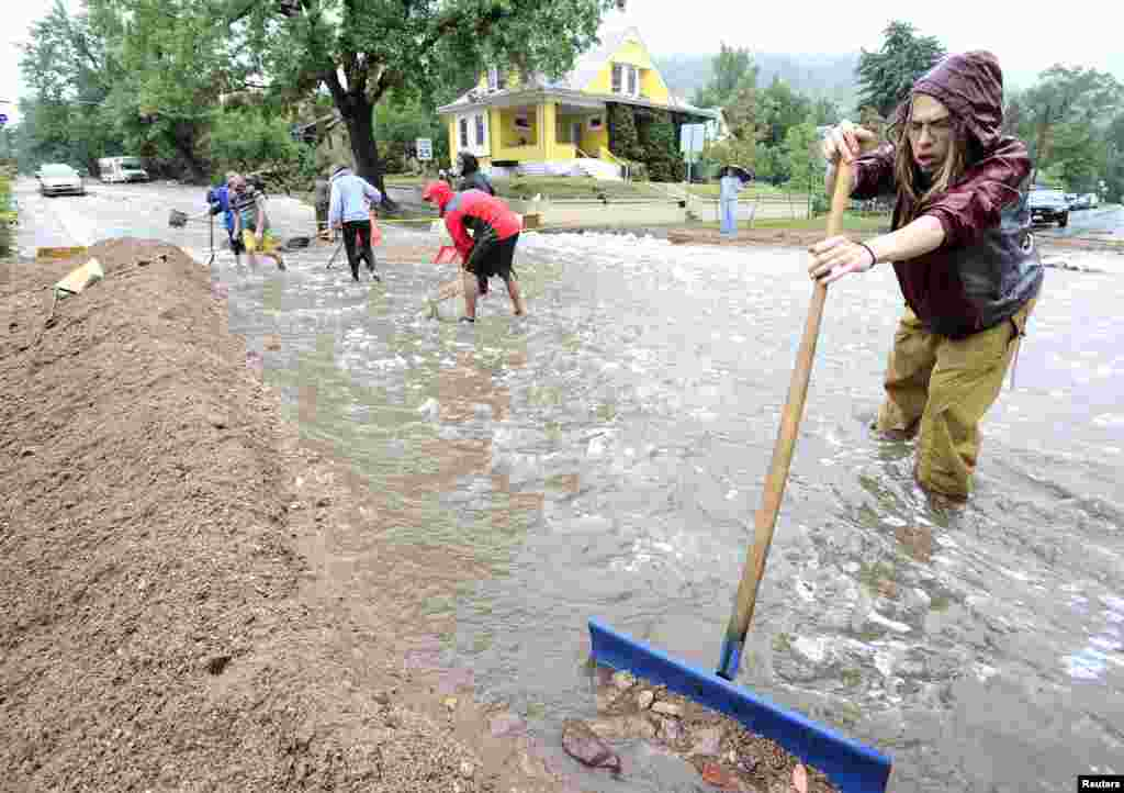 Nick Carter shovels debris as heavy rains cause severe flooding in Boulder, Colorado, Sept. 12, 2013.