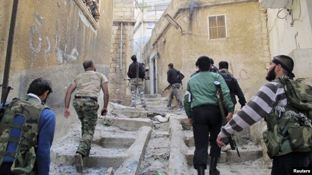 Members of the Free Syrian Army climb up stairs during a patrol in Haram town in Idlib Governorate, October 30, 2012.