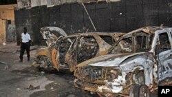 Polisi Somalia berjalan melewati rongsokan akibat ledakan di lokasi ledakan di Mogadishu, 4 Januari 2015.
