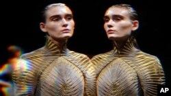 Un modèle, vu à travers un verre déformant, porte une création pour l'automne-hiver d'Iris Van Herpen, lors de la fashion week à Paris, le mardi 8 mars 2016. (AP Photo/Thibault Camus)