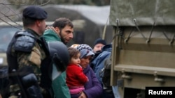 Macedonian soldiers escort migrants who have crossed the border illegally from Greece, into army trucks in the village of Moini, Macedonia, March 14, 2016. About 600 refugees who managed to cross over have been returned to greecce.