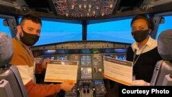 Precious Zimbabwe, right, and Abdulaziz Belkhair show off certificates for completing multicrew cooperation training on an Airbus 320 flight simulator. (Courtesy Photo: Precious Sibalo)