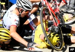 Britain's Chris Froome, wearing the overall leader's yellow jersey, right, Netherlands' Bauke Mollema, center, and Australia's Richie Porte crash at the end of the twelfth stage of the Tour de France cycling race.