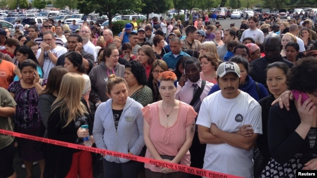 Parents wait behind police tape for students from Reynolds High School to arrive by bus in Troutdale, Oregon, June 10, 2014.