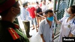 Người dân được kiểm tra thân nhiệt trước khi vào sân vận động xem bóng đá tại Nam Định hồi tháng 6/2020. Việt Nam vừa ghi nhận 2 ca tử vong vì COVID-19 sau 9 tháng không có người chết vì virus này.