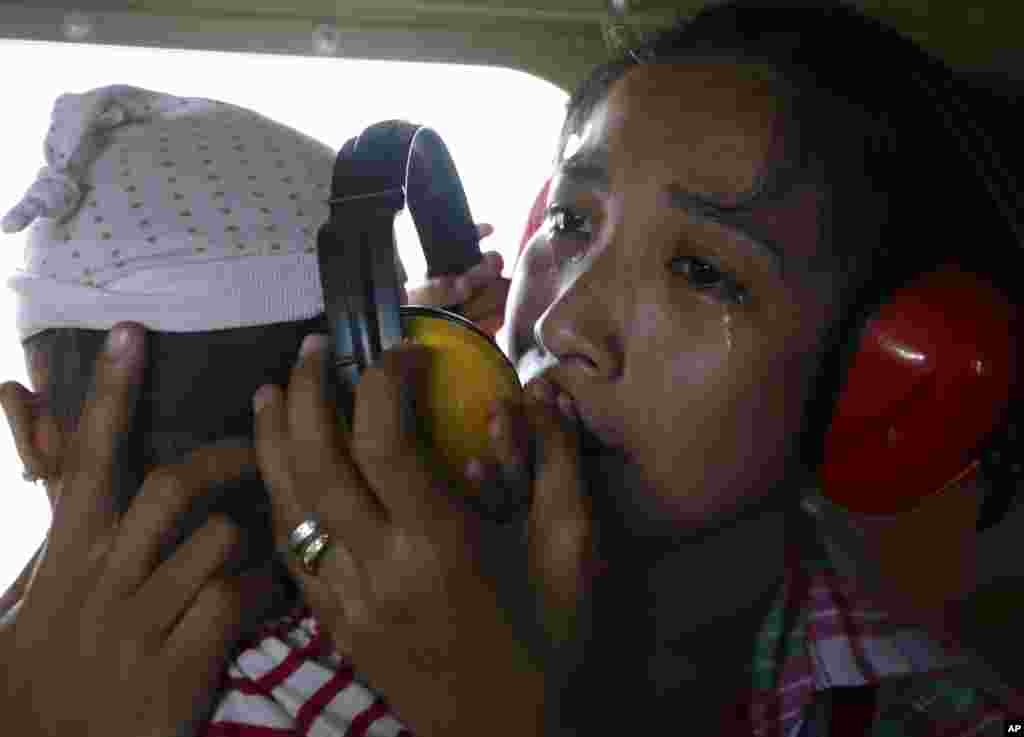 A mother cries in relief upon boarding a Philippine Air Force helicopter in Guiuan township, Nov. 11, 2013.