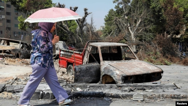 A woman walks past a burnt vehicle near Rabaa al-Adawiya mosque in Cairo, Aug. 28, 2013.