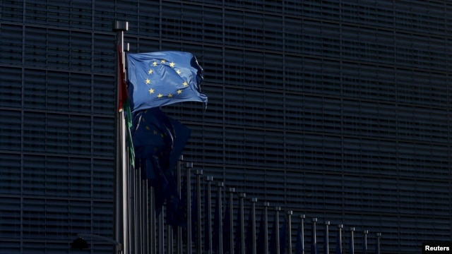 FILE - A European Union flag flutters outside EU Commission headquarters in Brussels, Belgium, Jan. 12, 2016.