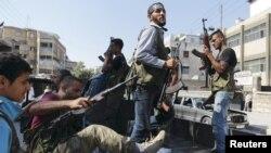 Các thành viên của quân đội Giải phóng Syria trên một chiếc xe tải chuẩn bị tiến vào thị trấn Salah Edinne trong thành phố Aleppo
