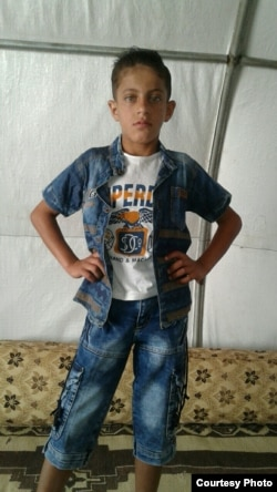 Khaled poses for a picture taken by his mother in their tent inside a refugee camp for orphans, in Idlib's countryside.