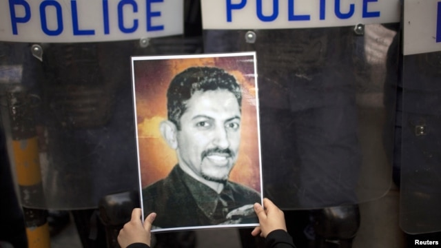 A protester holds a picture of Bahraini rights activist Abdulhadi al-Khawaja during an anti-government rally demanding his release, Manama, April 18, 2012.