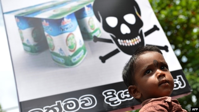 A Sri Lankan child looks on in front of a placard as pro-government activists demonstrate against the alleged contamination of milk powder in front of the factory of New Zealand dairy giant Fonterra in the Colombo suburb of Biyagama, August 22, 2013.