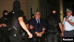 Pemimpin partai ekstrem kanan Yunani Fajar Emas, Nikolaos Michaloliakos, saat dibawa oleh polisi anti-terorisme ke pengadilan di Athena (2/10). (Reuters/Costas Baltas)