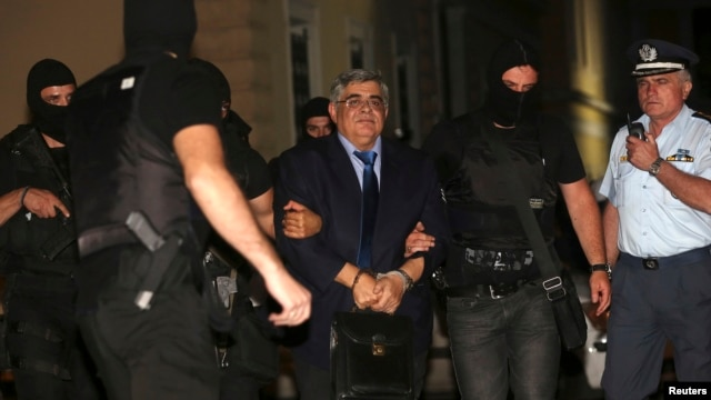 FILE - Extreme-right Golden Dawn party leader Nikolaos Michaloliakos is escorted by anti-terrorism police officers into a court house in Athens October 2, 2013.