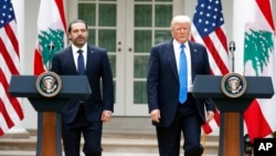 President Donald Trump and Lebanese Prime Minister Saad Hariri arrive in the Rose Garden of the White House in Washington, Tuesday, July 25, 2017, for a joint news conference. (AP Photo/Alex Brandon)