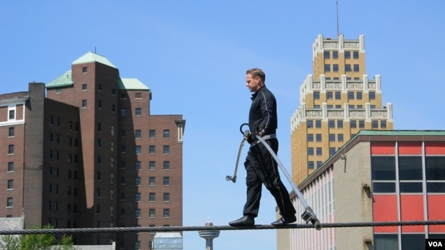 Nik Wallenda, on a wire three meters above a mostly empty parking lot, practices for his walk across Niagara Falls. (D. Robison/VOA)