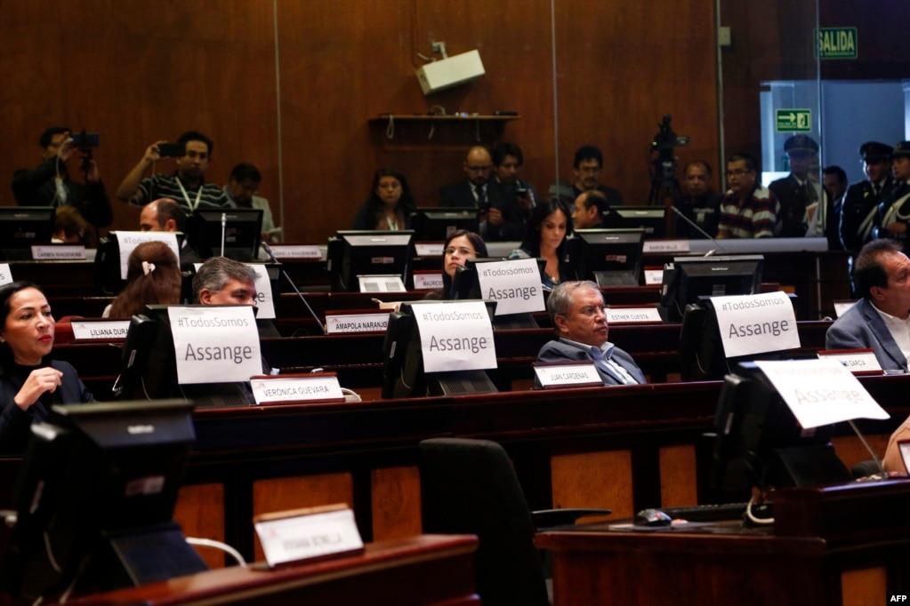 """영국 주재 에콰도르 대사관이 폭로 전문 사이트 '위키리크스'의 설립자 줄리안 어산지 씨의 보호조처를 철회함과 동시에 영국 경찰이 어산지 씨를 체포한 가운데, 에콰도르 의회에서 의원들이 """"우리 모두 어산지다""""라는 글이 적힌 종이를 자리 앞에 붙여놓았다."""