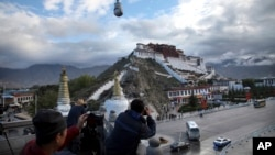 FILE - Tourists take photos of the Potala Palace beneath a security camera in Lhasa, capital of the Tibet Autonomous Region of China, Sept. 19, 2015.
