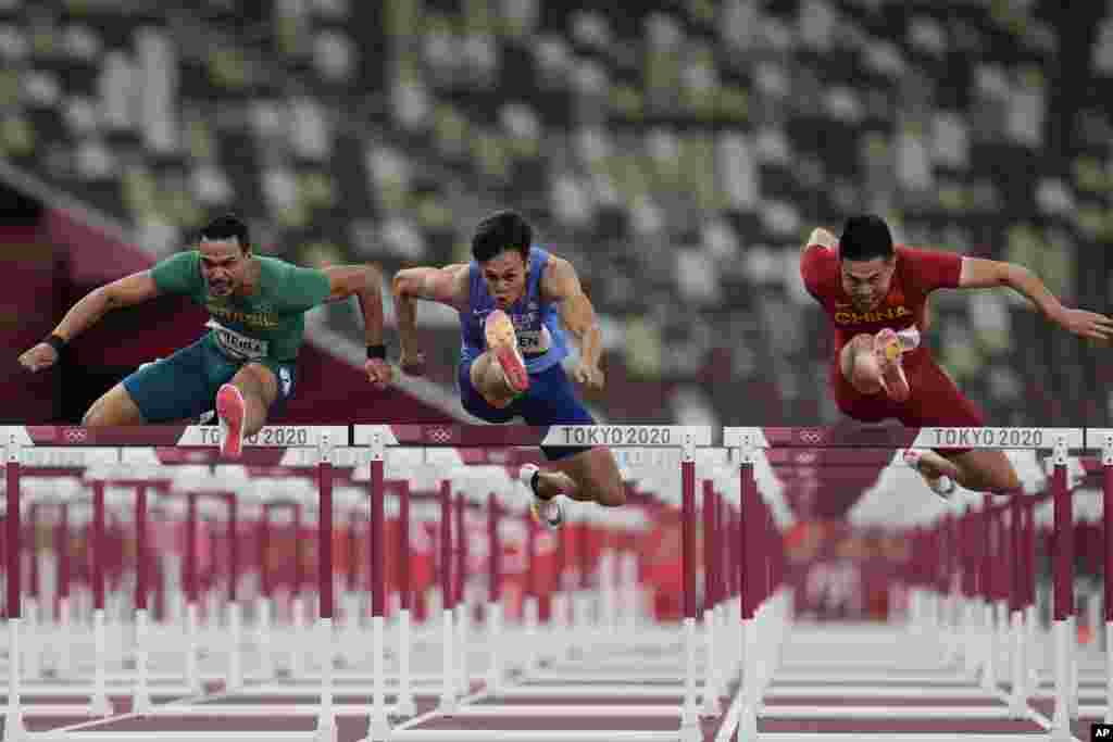 Rafael Pereira, left, of Brazil, Kuei-Ru Chen, of Taiwan, and Wenjun Xie,right, of China, compete in a heat of the men's 110-meter hurdles at the 2020 Summer Olympics, in Tokyo, Japan.