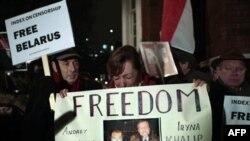 Рыдающая сестра арестованного кандидата в президенты Беларуси Андрея Санникова Ирина Богданова держит плакат с фотографиями брата и его супруги Ирины Халип во время акции протеста у посольства Беларуси в Лондоне. 21 декабря 2010 года