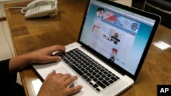 FILE - An Iranian checks the newly launched website of Iran's Intelligence Ministry, in Tehran, Iran