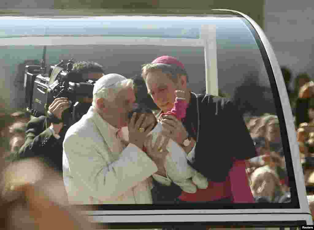 Pope Benedict XVI blesses a baby as he rides around St Peter's Square to hold his last general audience at the Vatican Feb. 27, 2013.