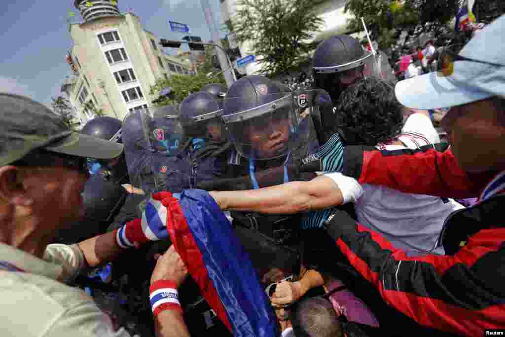 Policemen charge against anti-government protesters at one of their barricades near the Government House, Bangkok, Feb. 18, 2014.