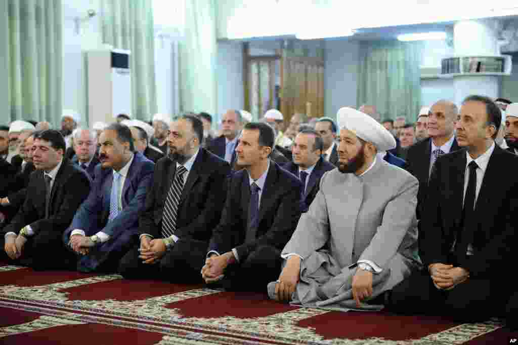 Syrian President Bashar Assad prays at the start of Eid al-Fitr at the Anas bin Malik Mosque, Damascus, August 8, 2013.
