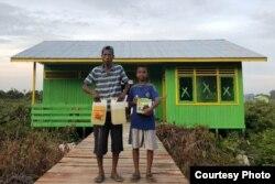 Seorang transmigran dan anaknya di depan rumah mereka di Kalimantan Utara. (Foto: Kemendes PDTT)