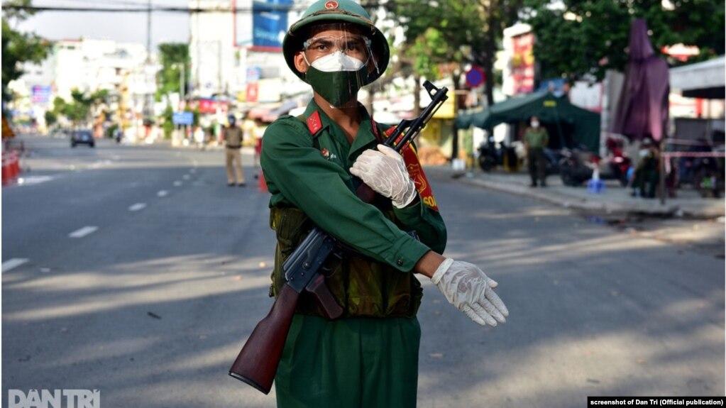 """Một quân nhân mang súng ở Tp.HCM hôm 23/8/2021 sau khi chính quyền ra chỉ thị """"dân không ra khỏi nhà""""."""