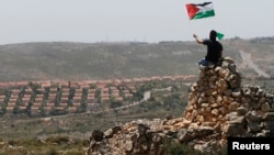 A protester waves a Palestinian flag in front of the Jewish settlement of Ofra during clashes near the West Bank village of Deir Jarir near Ramallah, April. 26, 2013.